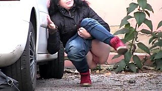 Dark haired filthy chick in red sneakers pisses near car outdoors