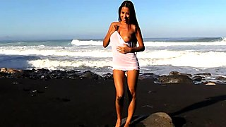 Beautiful naked babe on a black sand beach